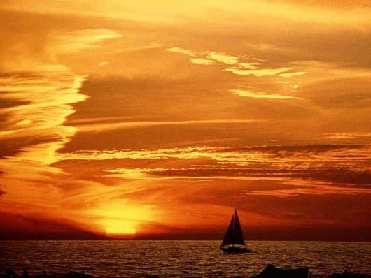 Foto Tramonto con barca vela